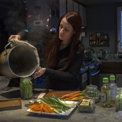Vegan chef Molly Aubuchon pours a brine over green beans that she decided to include last minute in her vegan sushi. The beans will sit a few hours before being rolled with other ingredients into the maki rolls by Aubuchon and her children for dinner Monday, Feb. 8, 2016 in her Kent, Ohio, home.