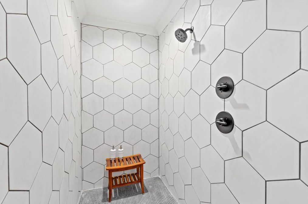 A long shower with white honeycomb tiles on the walls.