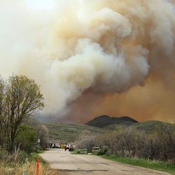 Thick smoke rises into the air as a wildfire burns in the Dutch Hollow area of Midway on Tuesday, May 12, 2020.