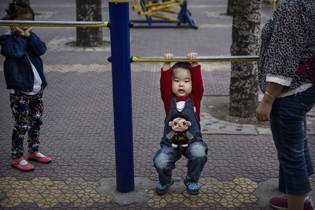 A young Chinese boy hangs from bars while exercising with his mother at a park on September 17, 2014, in Beijing, China.