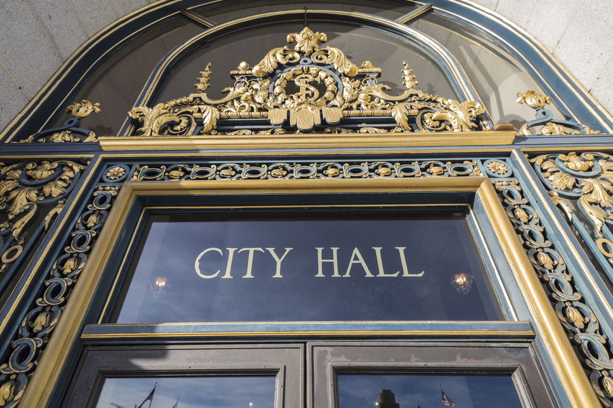 """Gold lettering that says """"City Hall"""" above the entrance to the building."""