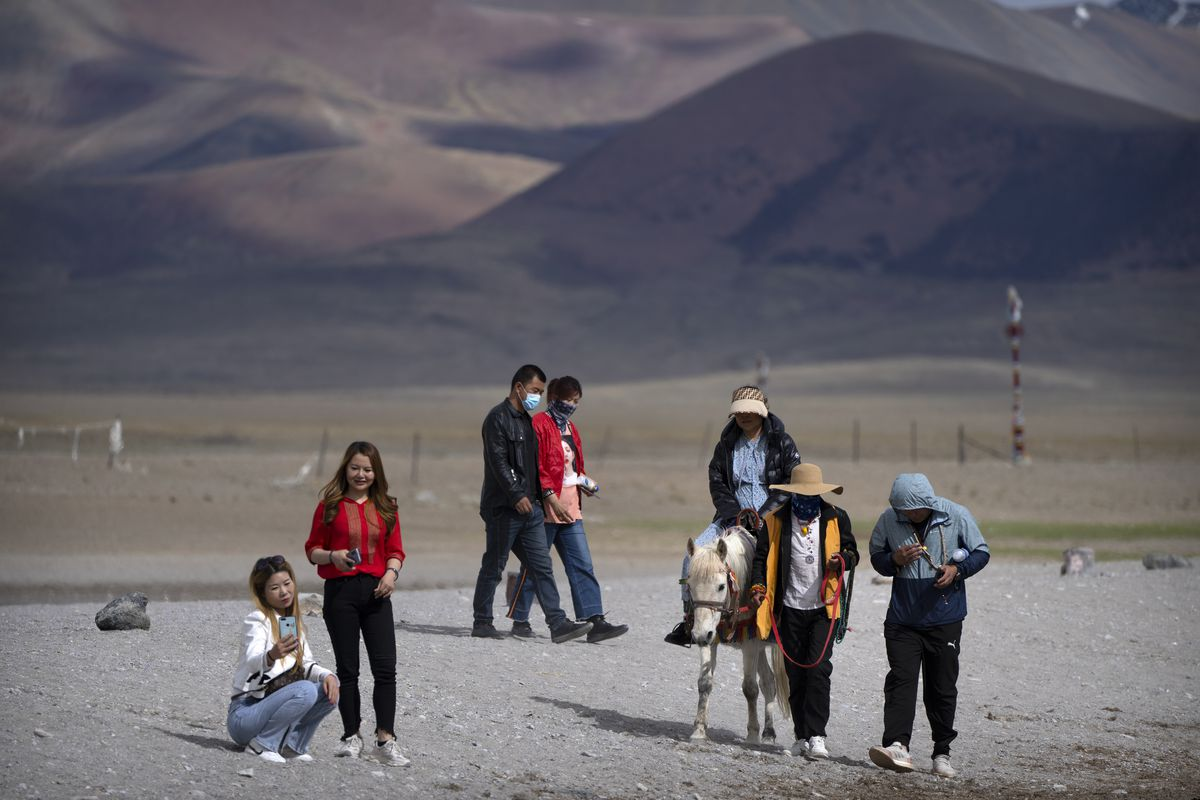 Tourists walk along the lake and ride ponies in Namtso, in western China's Tibet Autonomous Region.