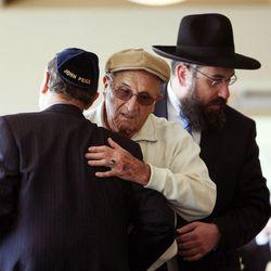 With Rabbi Benny Zippel at right, John Price, left, greets Holocaust survivor Abe Katz at the beginning of a Utah Holocaust Memorial Commemoration at the Jewish Community Center in Salt Lake City, Thursday, April 19, 2012.