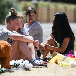 Sophie Fry, Kate Munger, Sydney Schmidt and Jessey Fournier, all 14, sit beside a memorial to the victims of Tuesday's fatal shooting on Alta Canyon Drive in Sandy on Wednesday, June 7, 2017.