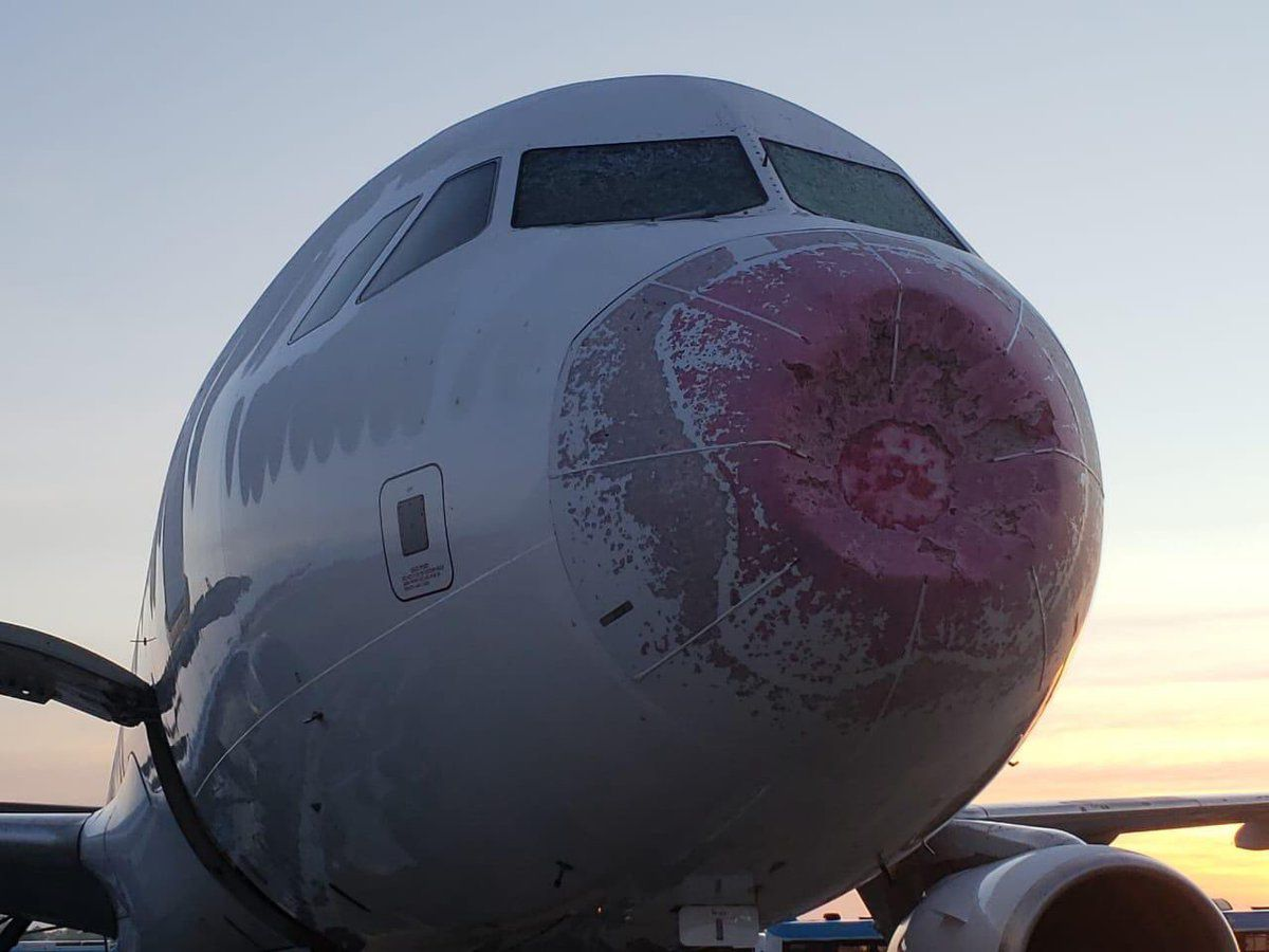 Flight JJ-8050 experienced turbulence and hail that caused both windshields to crack and a damaged nose cone.
