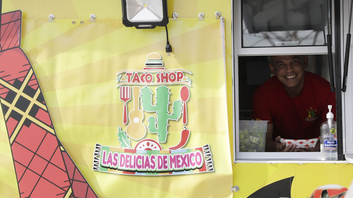 A man peers out of a yellow taco truck.