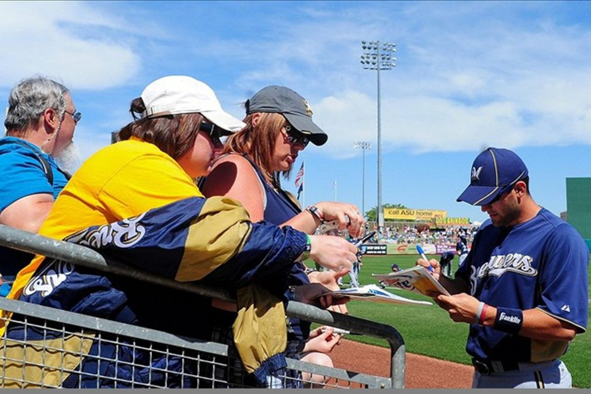 Mar. 14, 2012; Mesa, AZ, USA; Milwaukee Brewers shortstop Jeff Bianchi (65) signs autographs for fans prior to the game against the Chicago Cubs at HoHoKam Park.  Mandatory Credit: Matt Kartozian-US PRESSWIRE