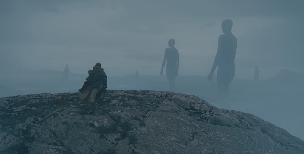 Gawain (Dev Patel) stands at the edge of a cliff, looking down into a misty grey valley where vast naked giants are walking toward the horizon