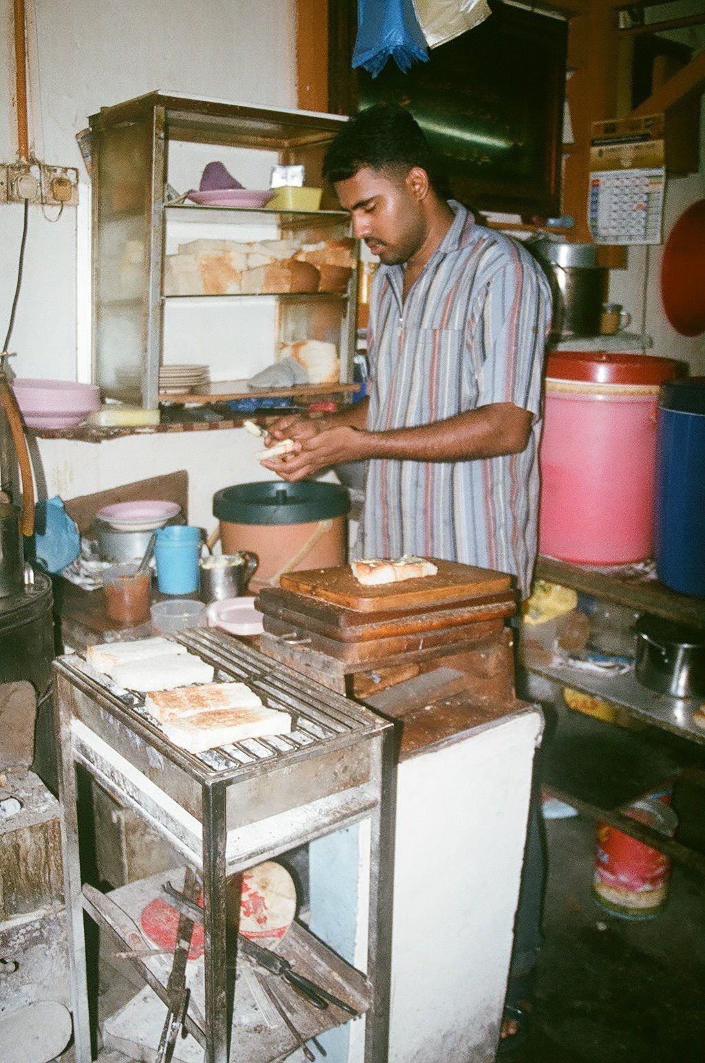 A cook at a kopitiam run by Eusope's great uncle in Penang prepares charcoal kaya toast