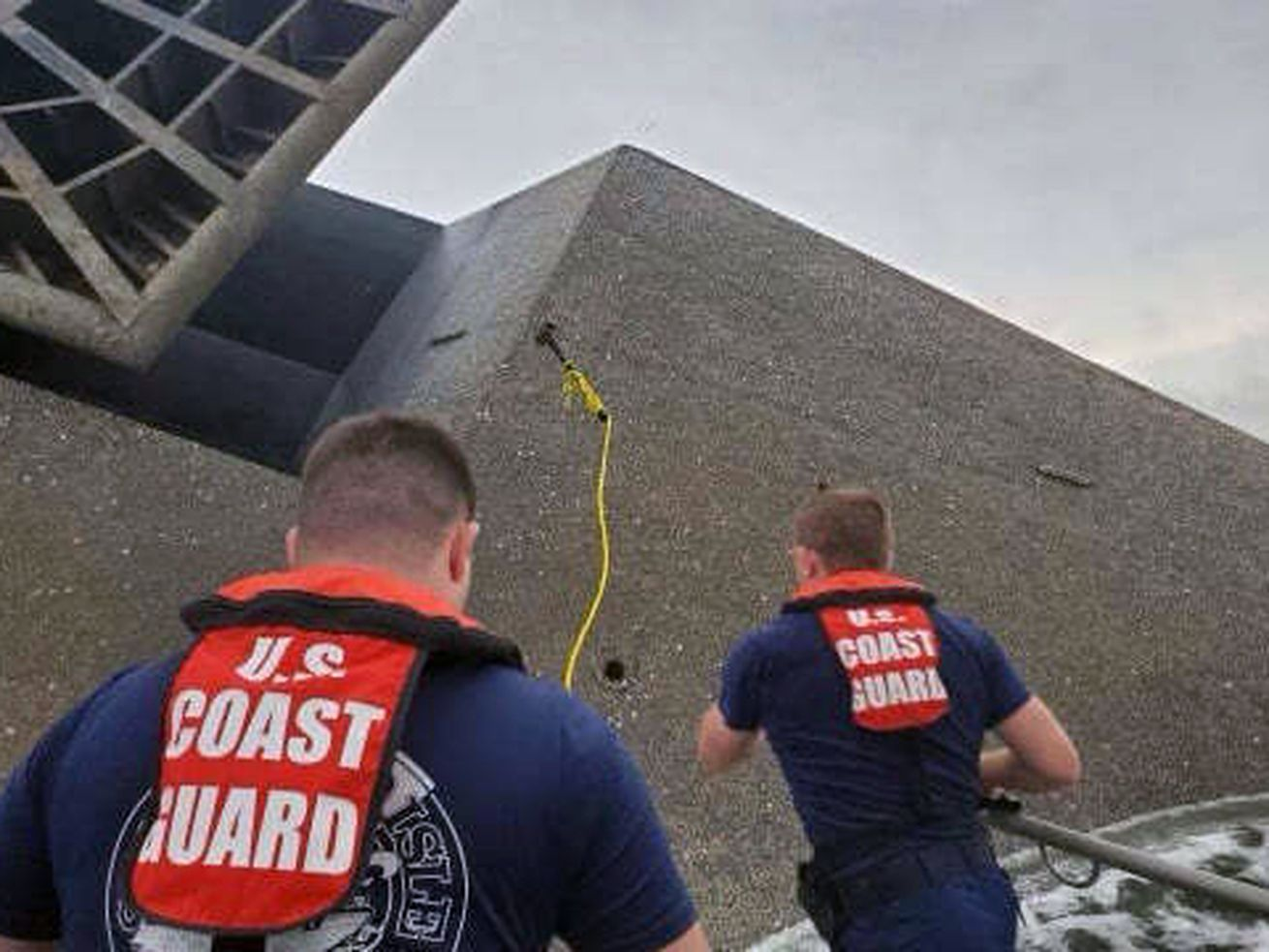 In this photo provided by the U.S. Coast Guard, Coast Guard Station Grand Isle 45-foot Response Boat-medium boat crew members attempt to throw a hammer at the hull of the SeaCor Power.