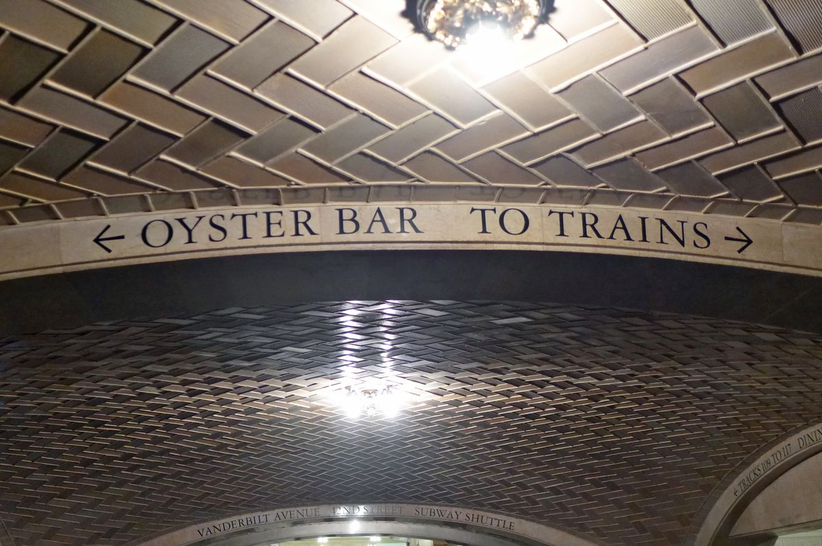 A sign near the ceiling of latticed tiles says Oyster Bar with an arrow pointing to the left, and To Trains with an arrow pointing to the right...