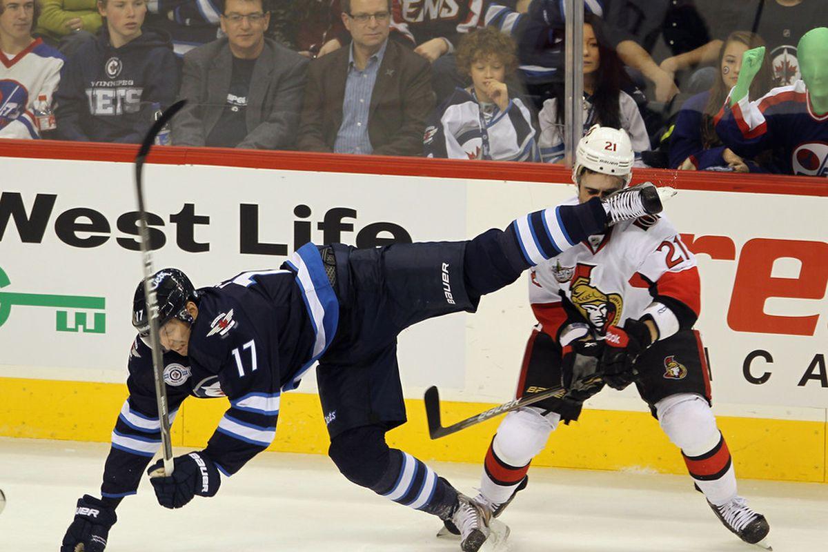 WINNIPEG, CANADA - NOVEMBER 29: The skate of Eric Fehr #17 of the Winnipeg Jets cuts Nikita Filatov #21 of the Ottawa Senators at the MTS Centre on November 29, 2011 in Winnipeg, Canada.