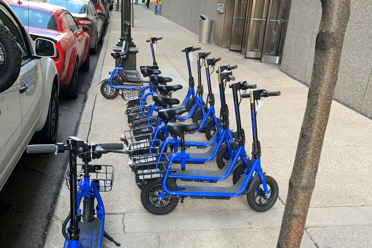 Bright blue e-scooters with seats are lined up on a sidewalk.