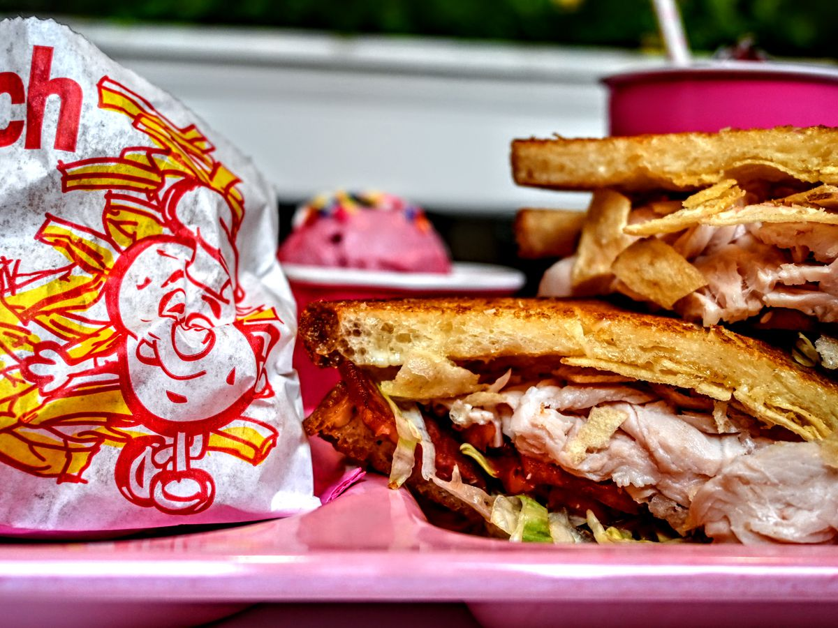 A sandwich of turkey, bacon, lettuce, and tomato on griddled bread, with a branded bag of fries beside on a bright countertop