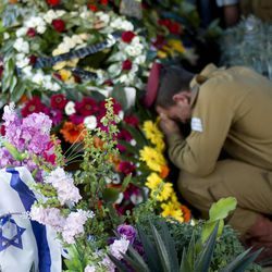 An Israeli soldier of the Maglan elite unit morns over the grave of Staff Sgt. Matan Gotlib, a Maglan elite unit soldier, during his funeral in the military cemetery in Rishon Letzion, central Israel, Thursday, July 31, 2014. Gotlib, 21, was killed in combat on Wednesday in the southern Gaza Strip.