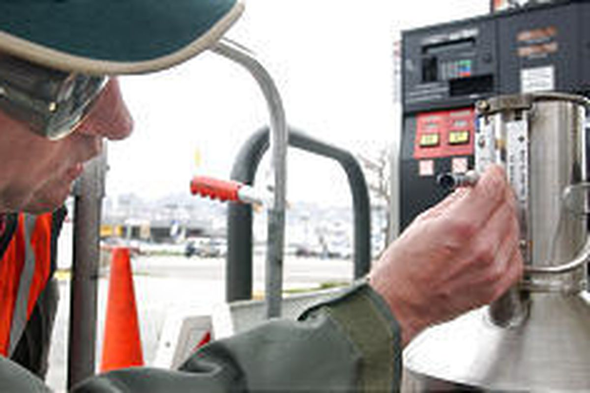 Dale Kunze, inspector with the Department of Agriculture, inspects accuracy of gas pumps at a 7-Eleven.