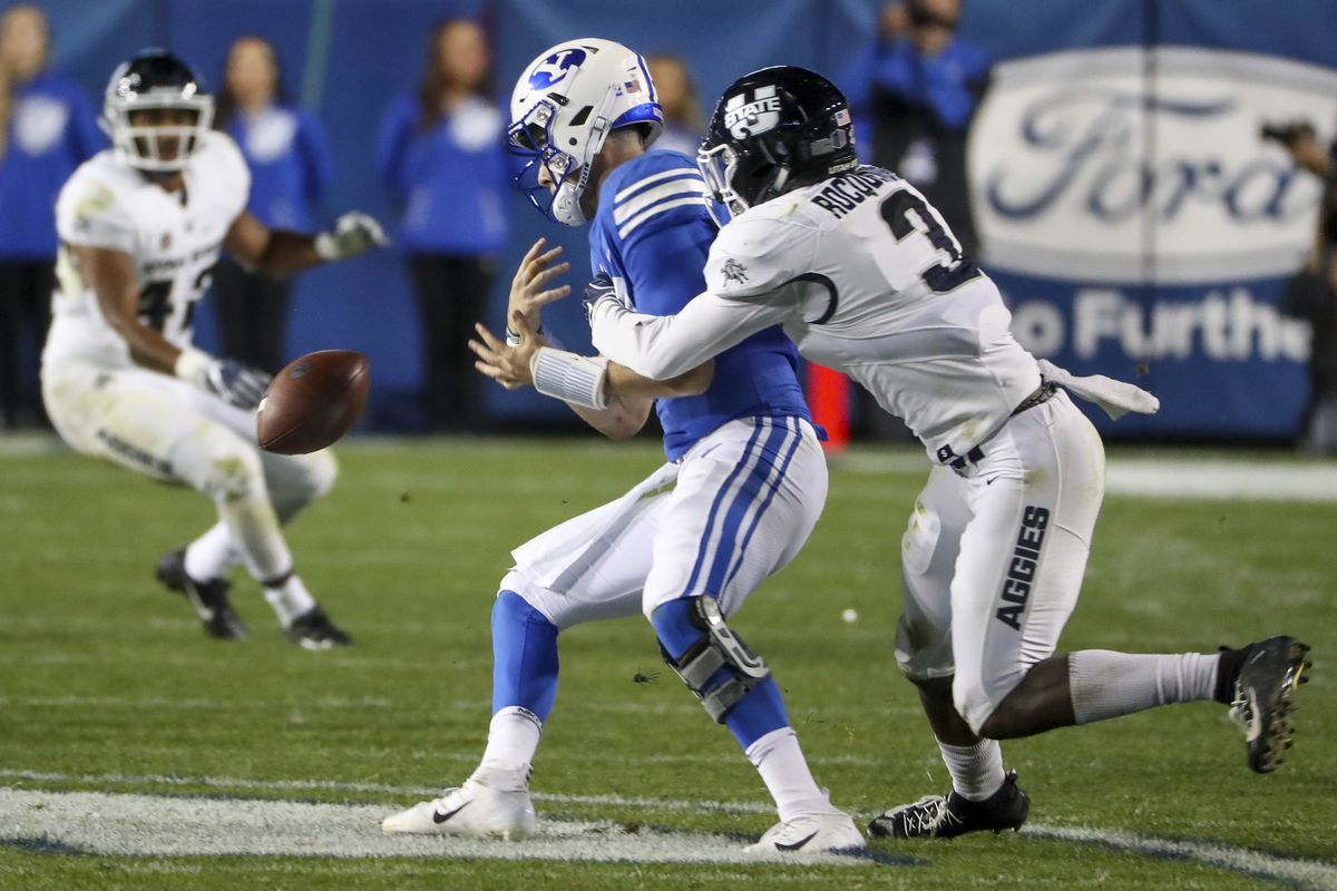 Brigham Young Cougars quarterback Tanner Mangum (12) gets stripped of the ball by Utah State Aggies safety Jontrell Rocquemore (3) during the Utah State versus BYU football game at LaVell Edwards Stadium in Provo on Friday, Oct. 5, 2018. Rocquemore recove