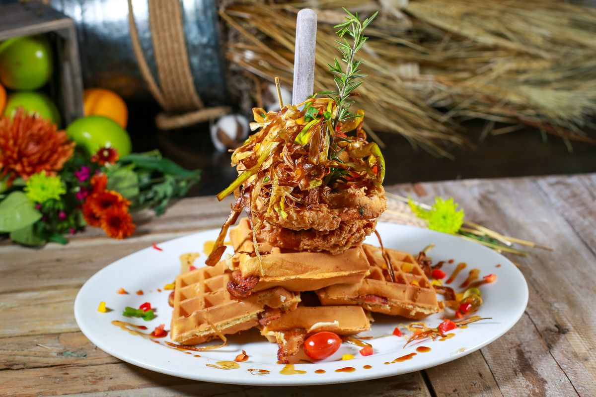 A white plate with chicken and waffles