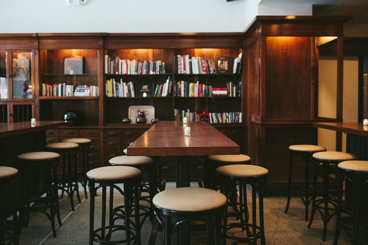 White bar stools surrounds long wood tables next to a library at Craft Work in West Village.