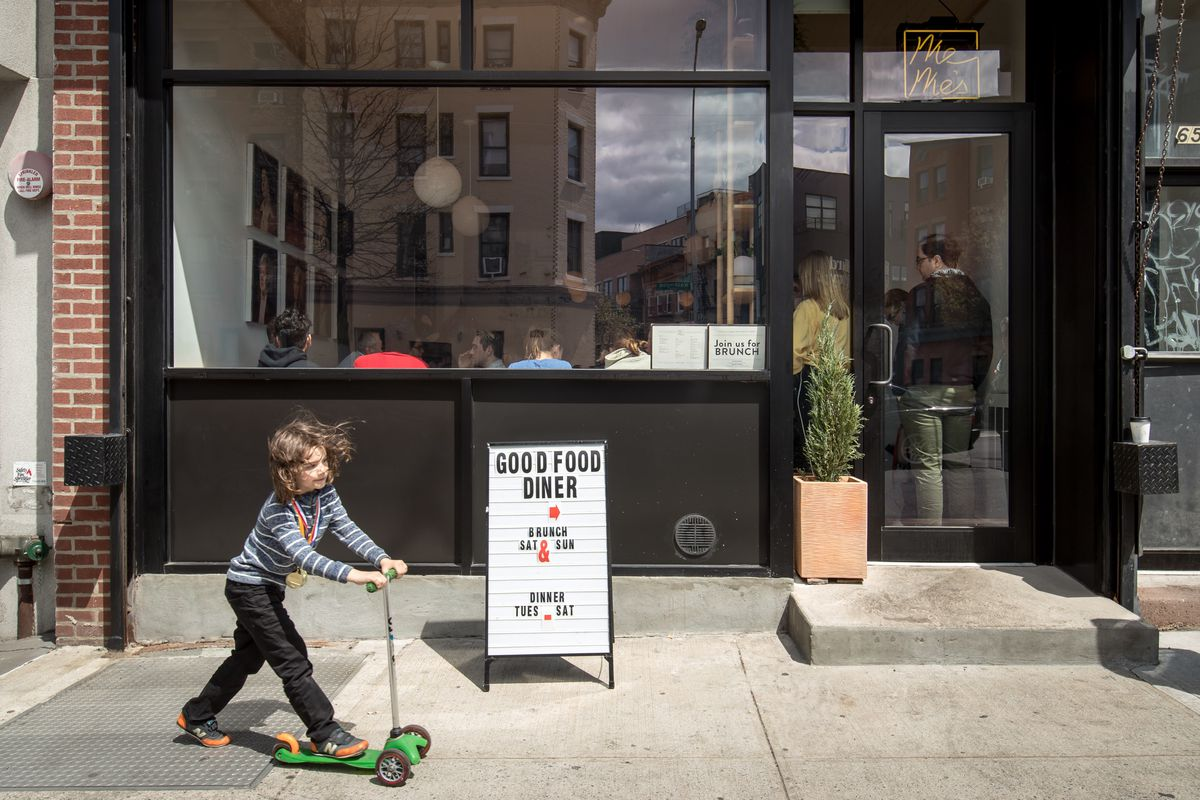 """A child stands in front of a restaurant on a scooter. They are next to a sign that points inside and reads: """"Good Food Diner"""""""