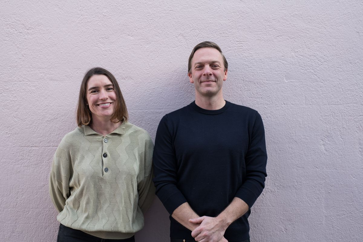 A woman, Jessica Baesler, and a man, Graham Files, stand in front of a lavender wall. She wears a grey shirt with a few buttons, while he wears a black long-sleeve shirt with his arms crossed in front of his waist. They both own Someday Bar on Division.