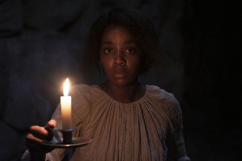 Cora enters a dark room, holding only a candle.