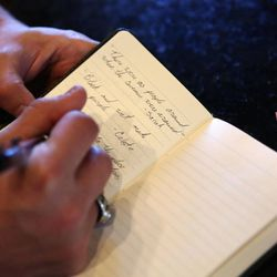 """Cory Simmons writes down funny quotes that family members have said such as, """"Black and wet make purple,"""" at home in Kamas on Saturday, Aug. 24, 2013."""