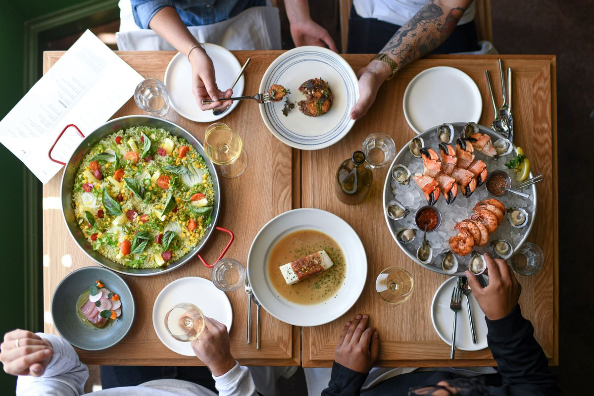 An overhead shot of a seafood feast with paella and other raw items.