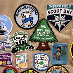 Patches cover the back of a Girl Scout's vest. | AP Photo