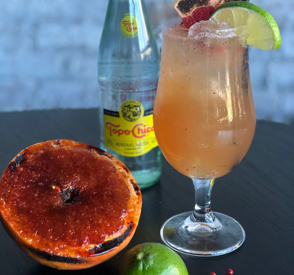 A charred grapefruit and bottle of sparkling water next to a cocktail.