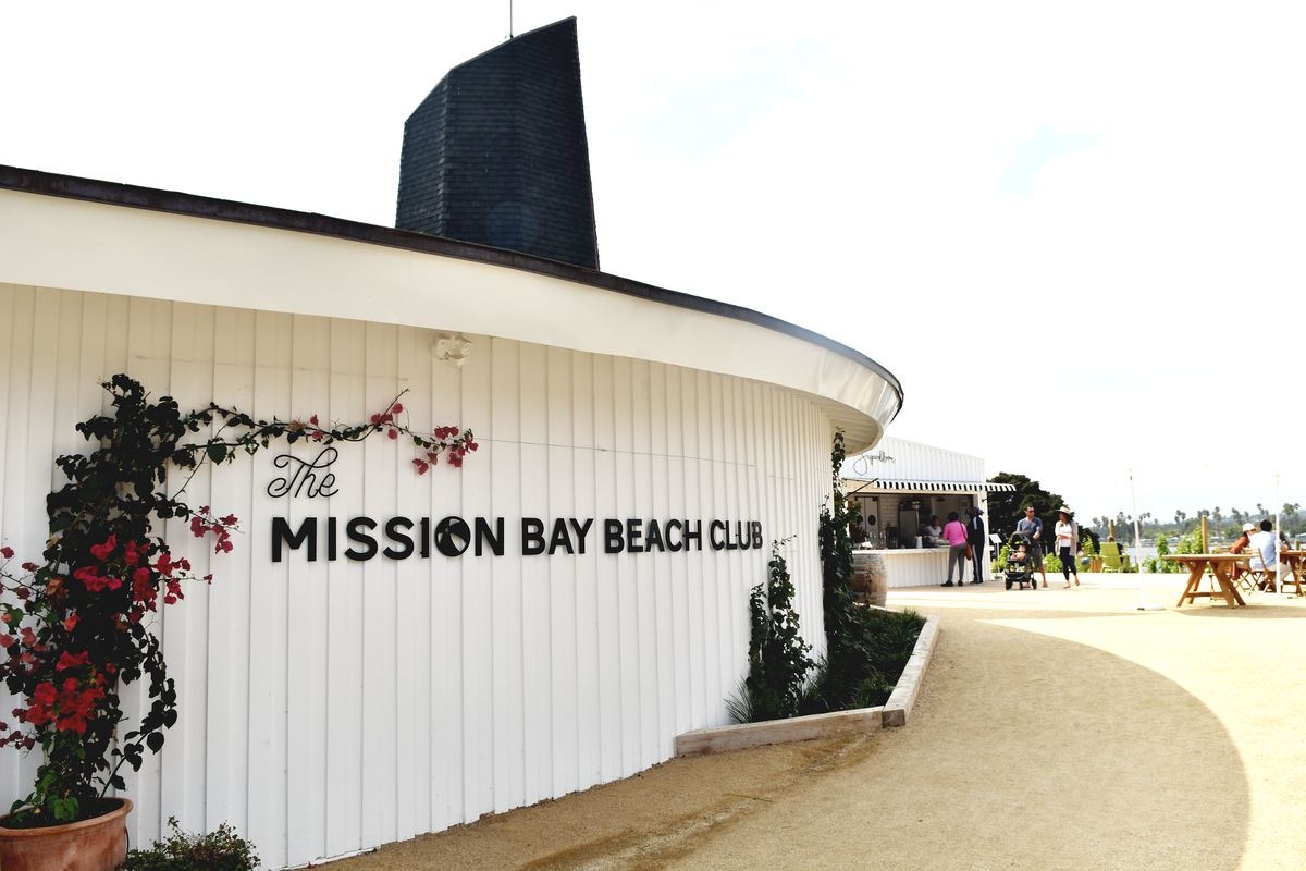 The Mission Bay Beach Club sign on the side of a building with a picnic table and people in the background.