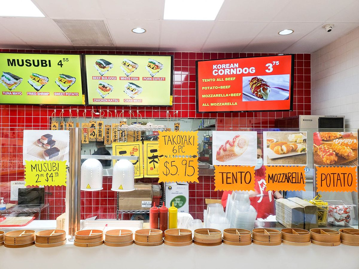 A red restaurant interior with bright yellow and orange menu signage.