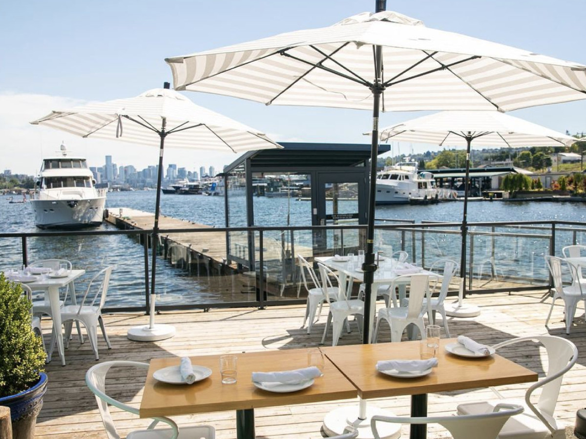 Light-colored umbrellas hang over tables on an outdoor patio with a boat and the Seattle skyline in the background overlooking Lake Union