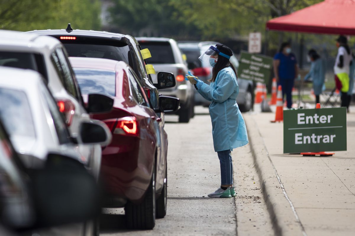 People arriving at a drive-thru testing site in Chicago are instructed about how to proceed.