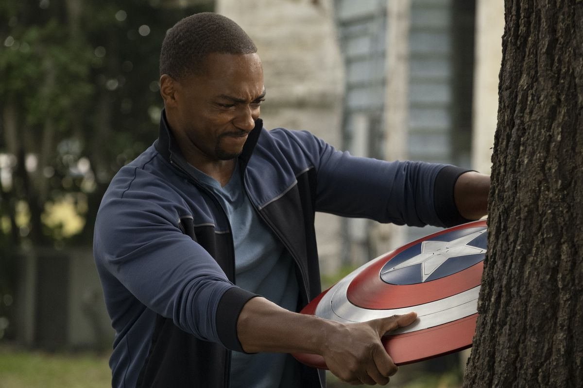 Falcon (Anthony Mackie) struggles to pull Captain America's shield out of a tree it's embedded in in Falcon and the Winter Soldier