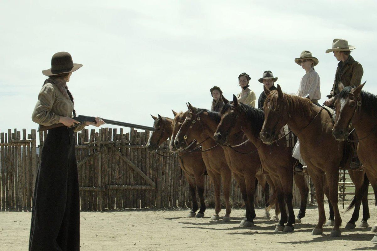 A woman with a rifle stands in front of a line of mounted horses