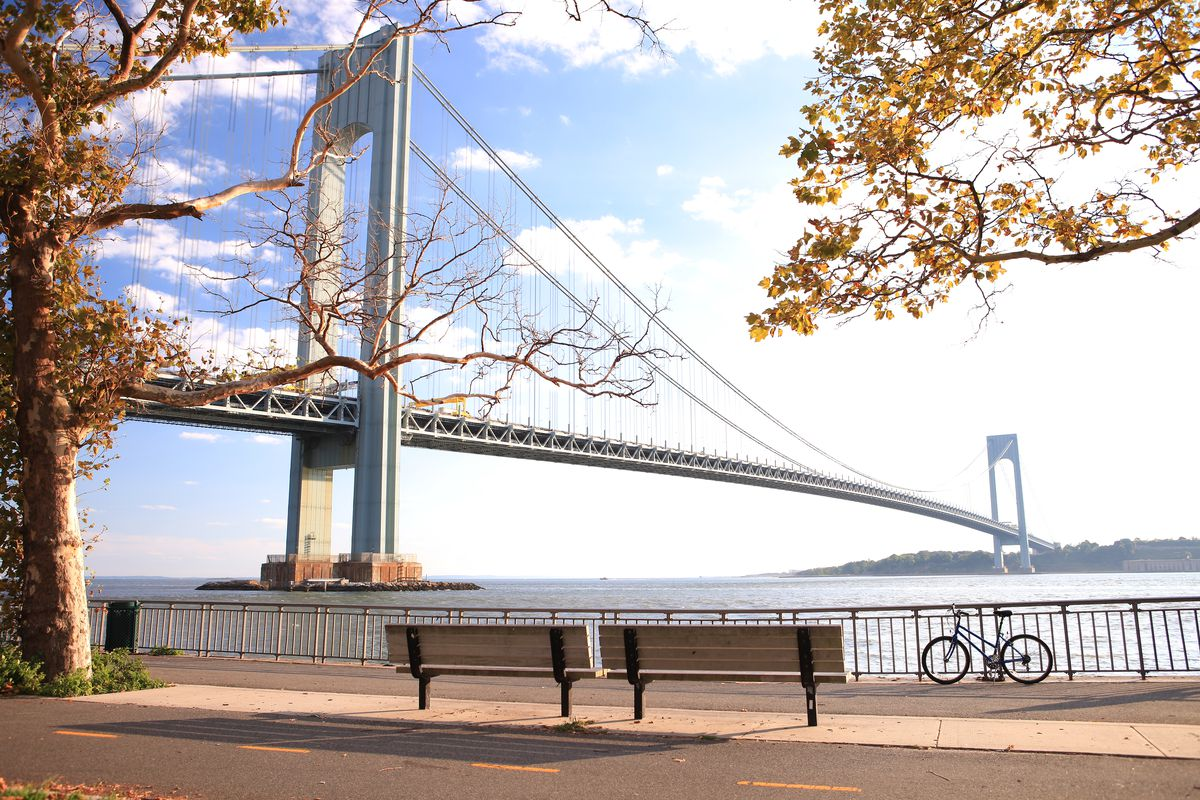 A bike is parked along a waterfront pathway with the Verrazzano-Narrows Bridge in the background.