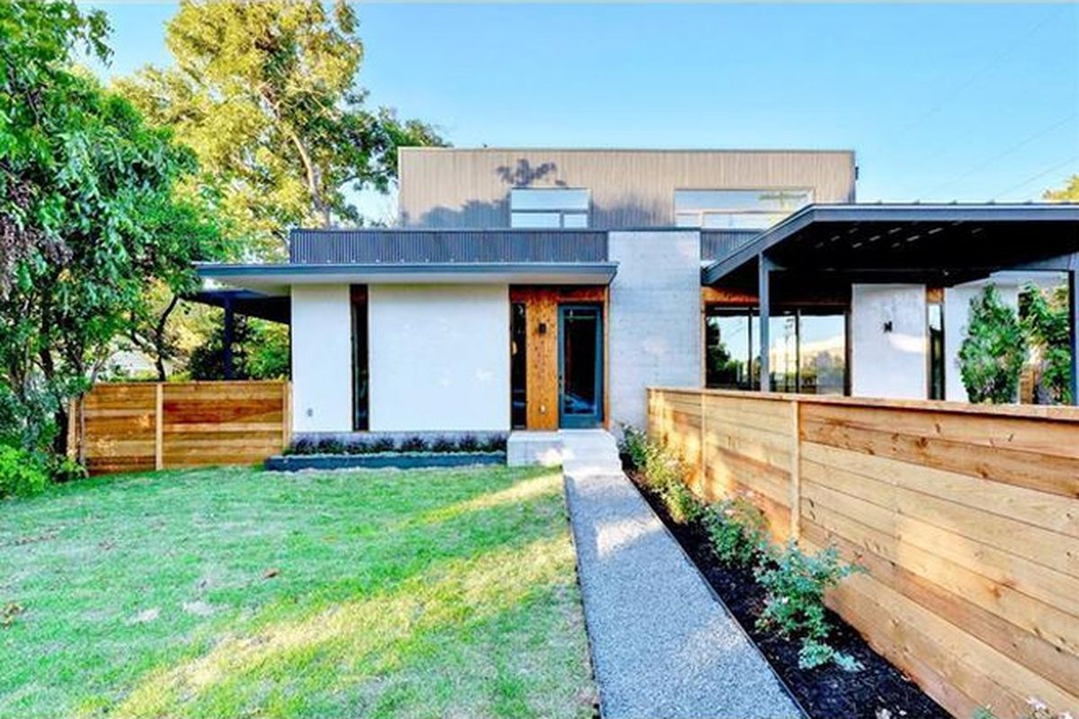 Contemporary white stucco duplex/condo with fence running down front yard