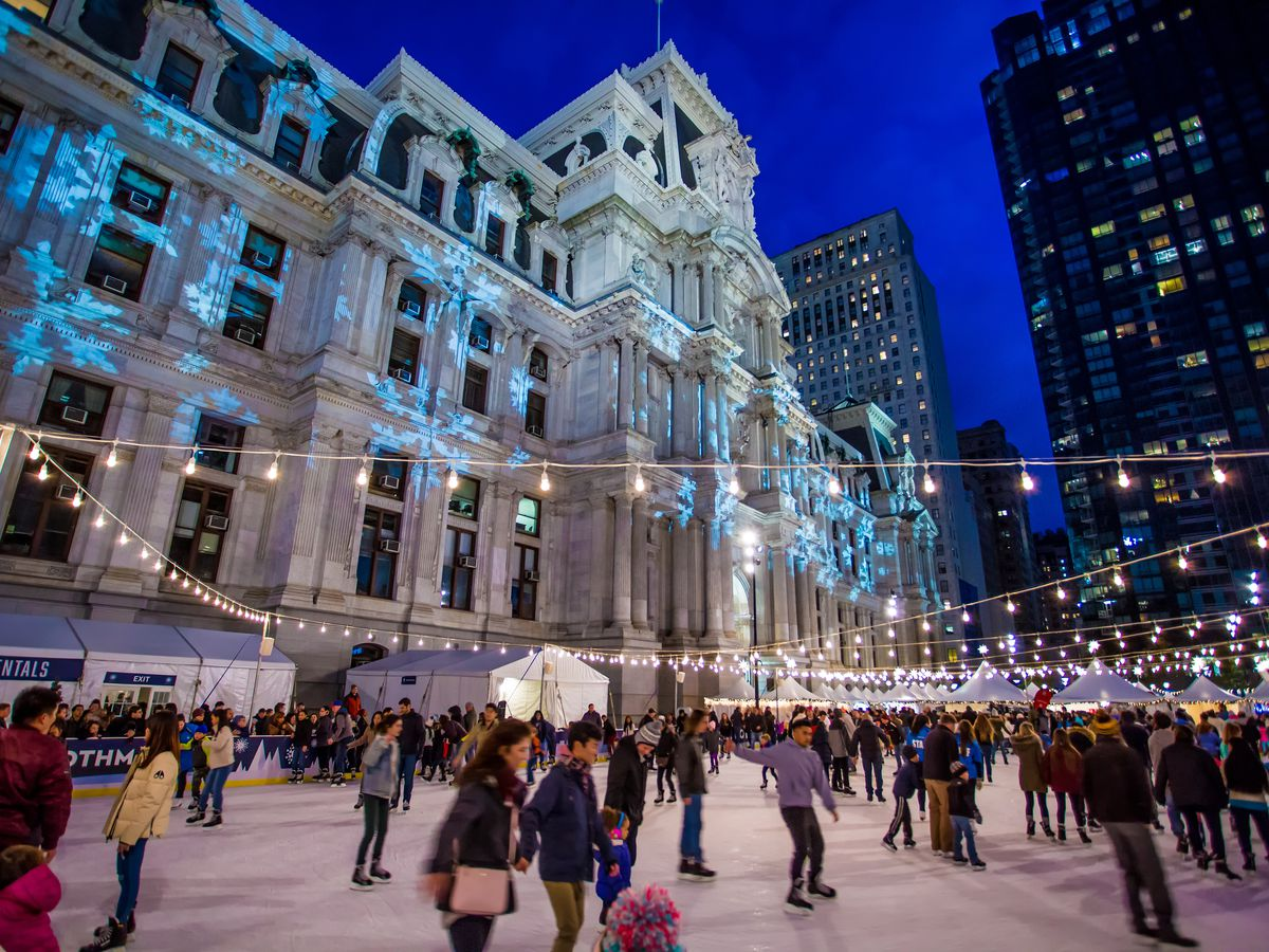 The Rothman Ice Rink in Philadelphia. There are many people skating on the ice. The rink is in front of Philadelphia City Hall.