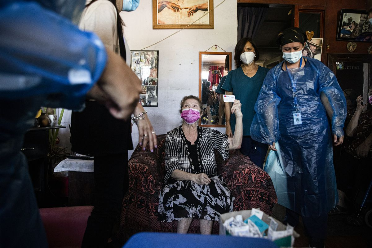 A woman in her home holds up a vaccination card after health care workers injected her.