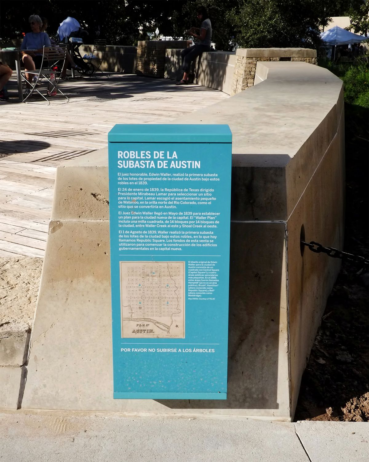 """A box attached to a stone wall with Spanish text and an old map displayed on it. The title is """"Robles de la Subasta de Austin."""""""