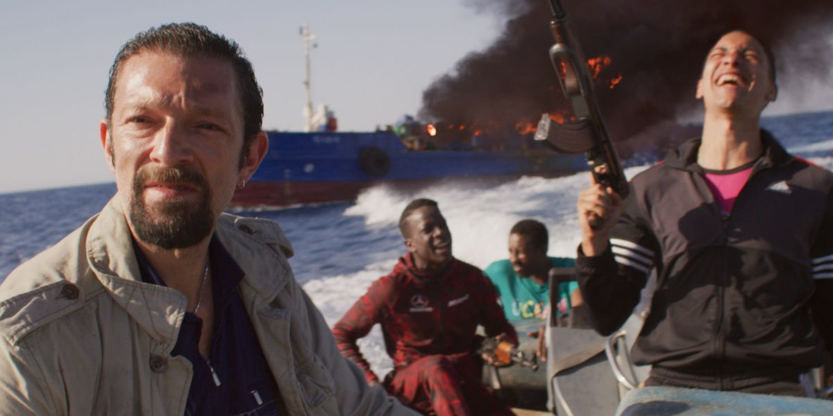 The World Is Yours: A gang of men rides away from a burning boat while brandishing an AK-47