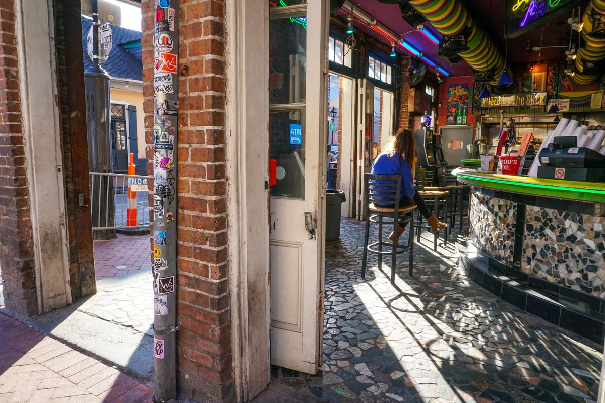 A woman sits at the bar inside the doors of a corner bar in the French Quarter in 2018