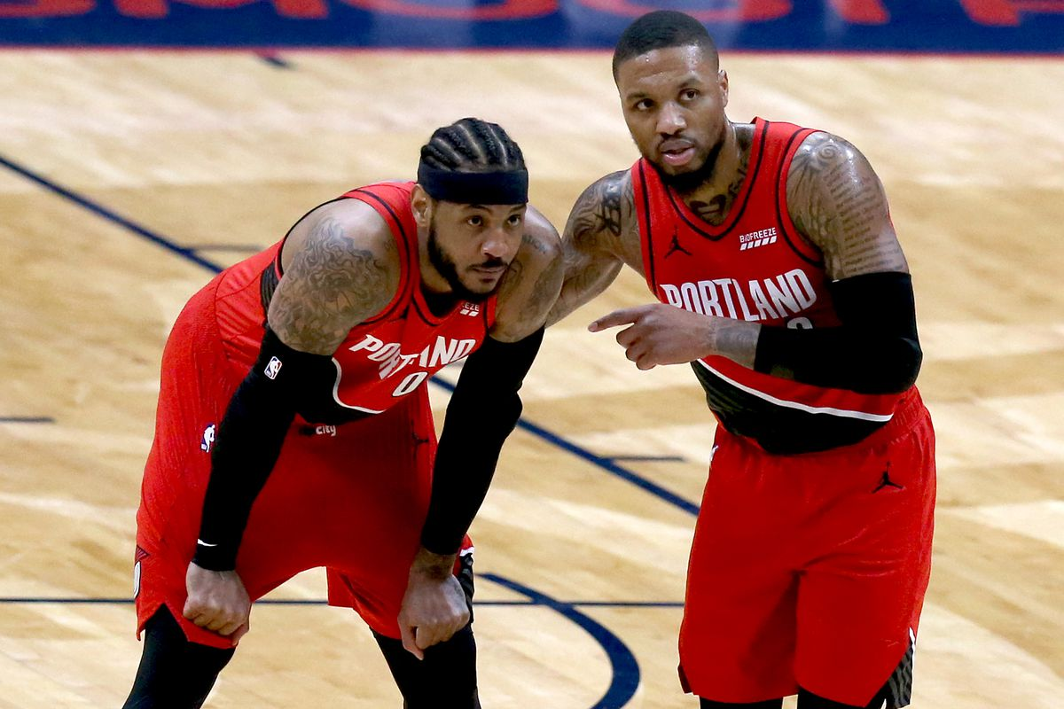 Damian Lillard of the Portland Trail Blazers and Carmelo Anthony of the Portland Trail Blazers stand on the court during the first quarter of an NBA game against the New Orleans Pelicans at Smoothie King Center on February 17, 2021 in New Orleans, Louisiana.