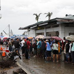 People wait in line at the airport to get on flights out of Tacloban, Friday, Nov. 22, 2013.