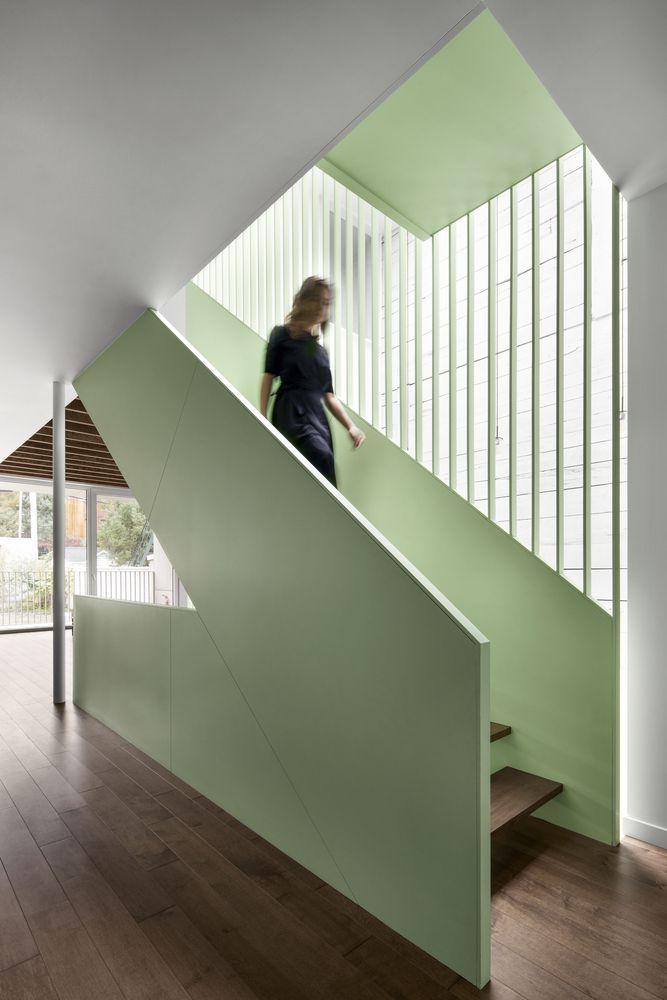 Woman walking down sage green stairs.