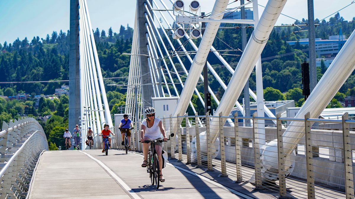 People ride bikes down a path on a striking white bridge with dramatic spans and views of evergreen-studded hills in the distance.