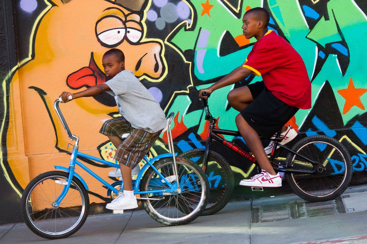 Two children are riding bicycles on a sidewalk. In the background is a colorful mural with graffiti.
