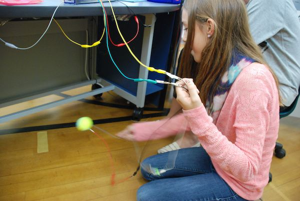 A student tests out her electronic piano, played using a tennis ball.