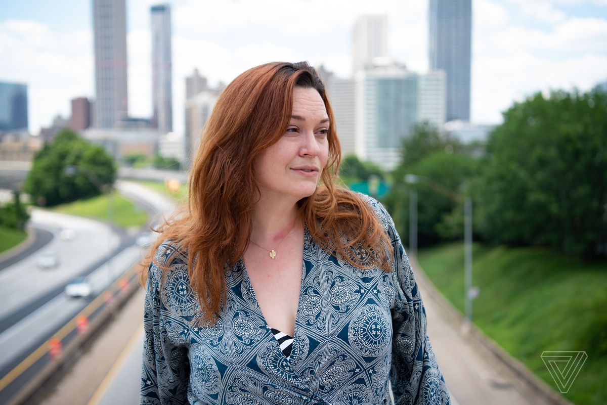 Sarah Owings stands outside for a portrait on an overpass with a highway in the background.